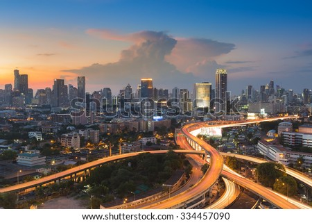 Sunset of Cityscape with highway interchange overpass during busy hour - stock photo