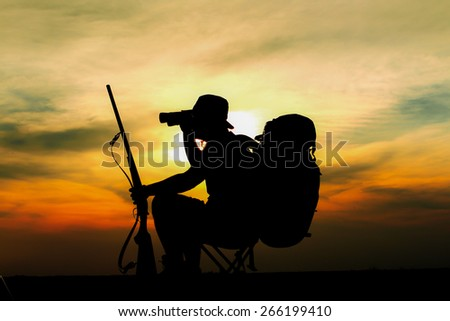 Sunset of hunter sitting on little chair with rifle, backpack and hat