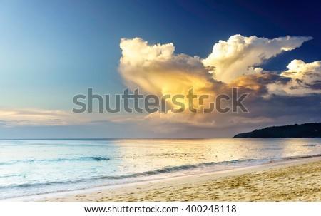Sunset on a beach with fantastic sky. Sunset light reflection, Phuket, Thailand. Sea sunset, Thailand. Amazing sunset. Soft sunset reflection in sea water at Karon beach, Phuket. Exotic sunset clouds - stock photo