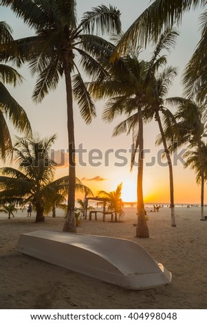 Sunset on a beautiful beach on the Caribbean coast. Boat on beach. Isla Mujeres, Mexico - stock photo