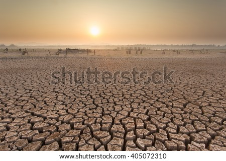 sunset on a died and cracked soil in arid season - stock photo