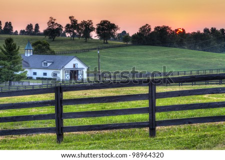 Sunset on a horse farm - stock photo