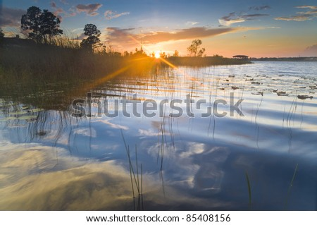 Sunset on a lake with reflection of sky in the water