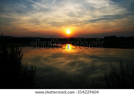 Sunset on a river, with big red sun reflecting, horizontal image - stock photo