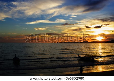 sunset on Andaman sea with silhouettes of boats, people and islands on horizon, Ao Nang beach, Krabi, Thailand    - stock photo