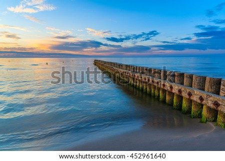 Sunset on beach with a wooden breakwater in Leba, Baltic Sea, Poland