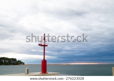Sunset on docks on the Mediterranean sea with red steel look-out post and white lighthouse in the cloudy background near Porec in Croatia - stock photo