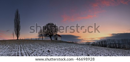 Sunset on frozen field with a chapel. - stock photo
