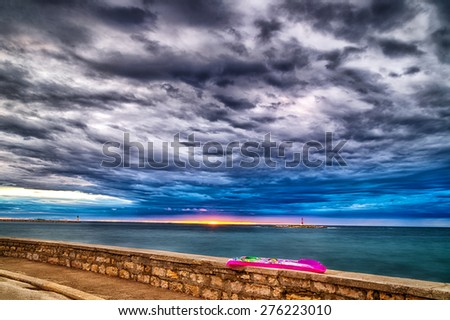 Sunset on inflatable mattress on parapet in front of the Mediterranean sea with red steel lookout and green top white lighthouse in the cloudy background near Porec in Croatia - stock photo