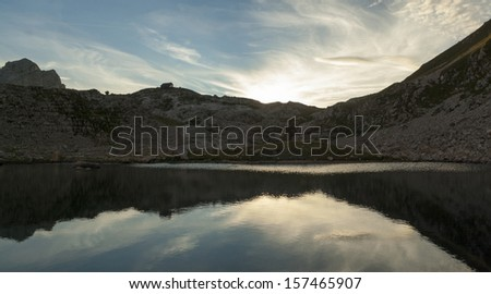 sunset on lake in slovenian alps, beneath zasavska koca cottage