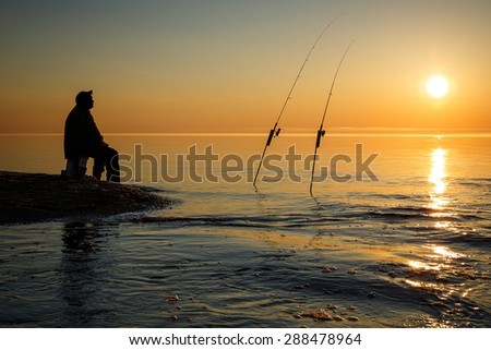 Sunset on  Lake Superior near Pictured Rock National Lake Shore Michigan State with silhouette of fisherman - stock photo