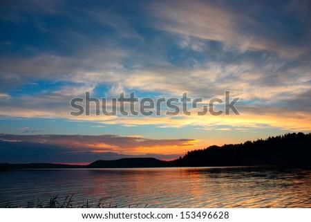 Sunset on lake under blue sky, quiet evening landscape - stock photo
