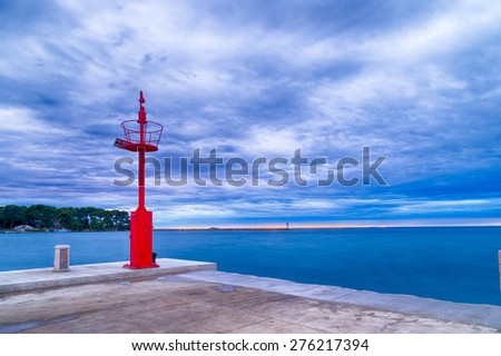 Sunset on pier on the Mediterranean sea with red steel lookout and white lighthouse in the cloudy background near Porec in Croatia - stock photo