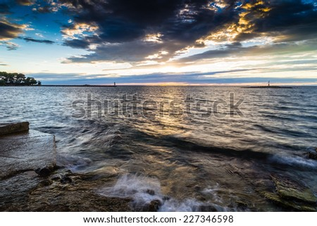 Sunset on prefabricated breakwater on the Mediterranean sea with with red steel lookout lighthouse on small island  green top white lighthouse in the cloudy background near Porec in Croatia - stock photo