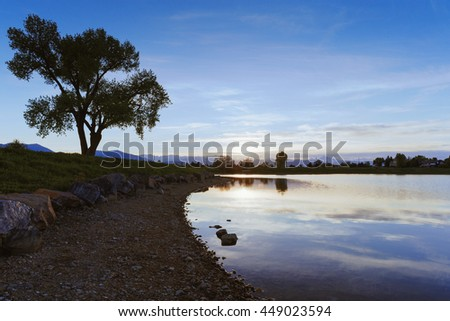 Sunset on rocky lake shore with large tree in distance, Louisville, CO - stock photo