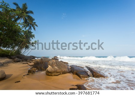 Sunset on sandy beach with palm trees, rocks and blue sky. Yellow sand, tropical island on vacation. - stock photo