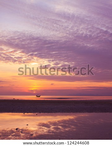 Sunset on sea during ebb with small fisherman boat on horizon - stock photo