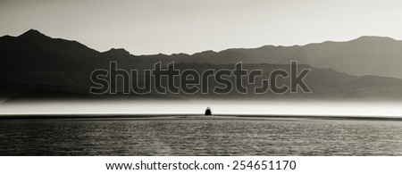 Sunset on Sea of Cortez (Cortes) with haze, mist, mountains, and fishing boat in the distance - stock photo