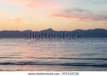 Sunset on the beach with beautiful sky, Majorca. Seaview sunset with beautiful pink sky. Summer sunset near mountains and sea. Calm sea at sunset. Sunset reflection in sea. Soft pink sunset in Majorca - stock photo