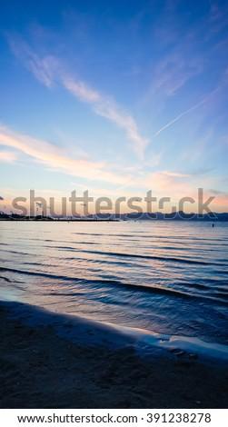 Sunset on the beach with beautiful sky. Summer sunset sea beach. Misty sunset sky. Sea breeze at sunset. Sunset twilight. Sunset skyline. Blue sunset. Sunset reflection on sea. Light cloudy sunset - stock photo