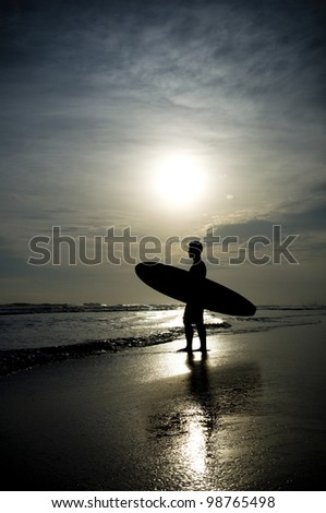 Sunset on the beach with surfer watching waves. - stock photo