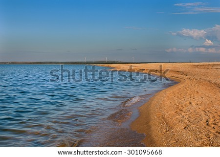 Sunset on the beach with windmills - stock photo