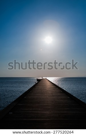 Sunset on the big pier. fantastic tranquil scene of a pier in the sea with fog and the sky above - stock photo