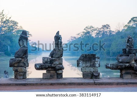 Sunset on the causeway to the South Gate of Angkor Thom with Gods and demons pulling on a giant snake leading to  the city built by King Jayavarman VII 1190-1210