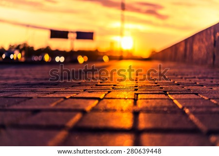 Sunset on the city waterfront. View of the flow of cars from the level of the pavement, image in the orange-blue toning - stock photo