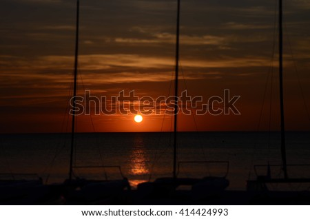 Sunset on the coast of Jamaica. Small boats on the shore.