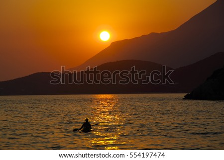 Sunset on the coastline of Turkey, near Kas. Man on a canoe.