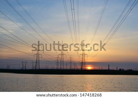 Sunset on the lake and transmission power line. Little noise - stock photo