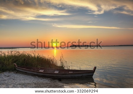 Sunset on the lake, fishing boat on the shore