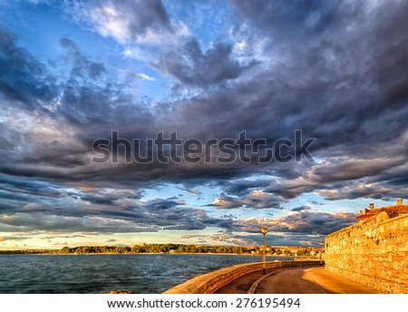 Sunset on the Mediterranean sea with a cloudy background near Porec in Croatia - stock photo