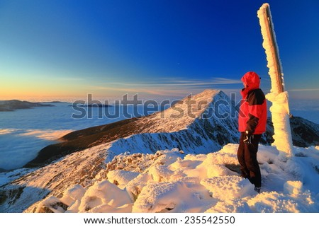 Sunset on the mountain summit and woman admiring the view during winter - stock photo