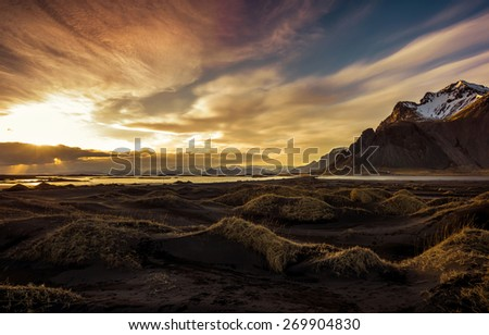 Sunset on the mountains and volcanic lava sand dunes by the sea in Stokksness, Iceland. The brown bushes are lavender plants desiccated in the winter but will flourish and bloom when spring comes. - stock photo