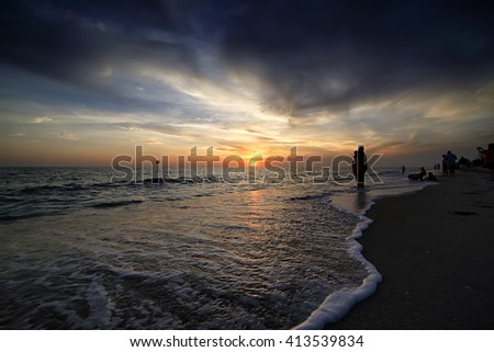 Sunset on the ocean. Silhouette of group of people hanging out and enjoy sunset  - stock photo