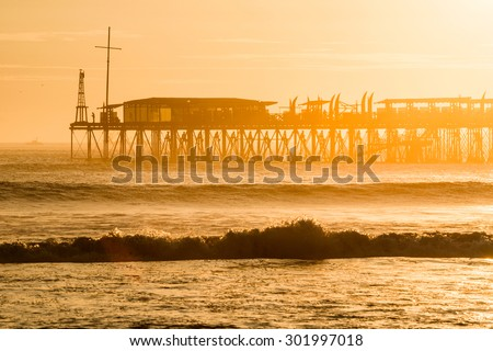 Sunset on the Pacific Ocean, the sun breaks through the mist and famous pier at Pimentel. Peru, South America
