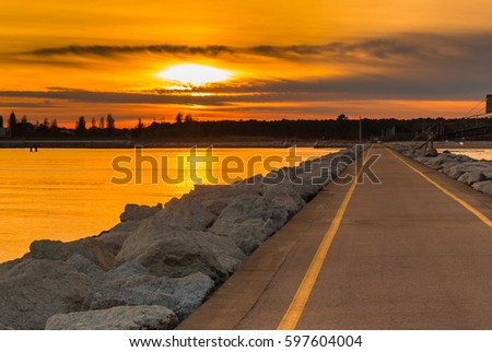sunset on the pier paved road leading to the coast