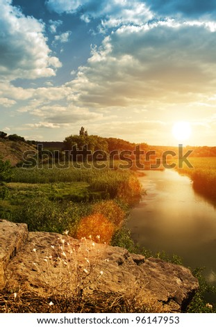 sunset on the river and green meadow