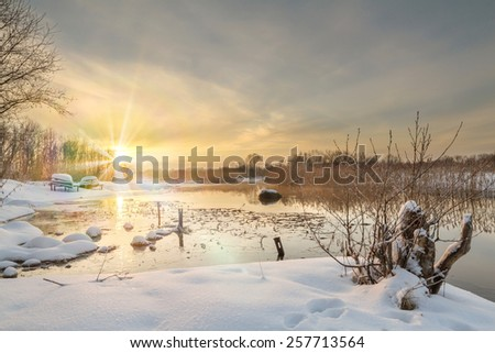 Sunset on the river in the winter in frosty weather with fog. Bright sunny winter day at the river. Bright sunny fine winter day. Sun beams. - stock photo