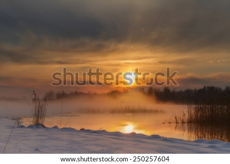 Sunset on the river with fog in the winter - stock photo