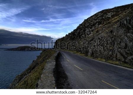 Sunset on the road in Dingle peninsula coastline - stock photo
