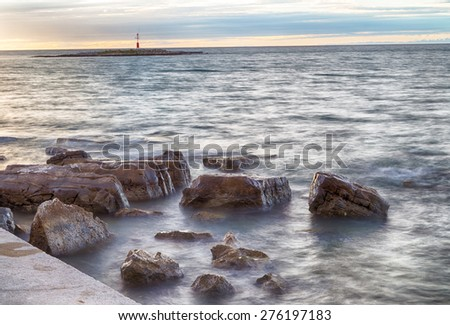 sunset on the rocks of the Mediterranean sea with red lighthouse on a small island in the background in Porec, Croatia in Europe