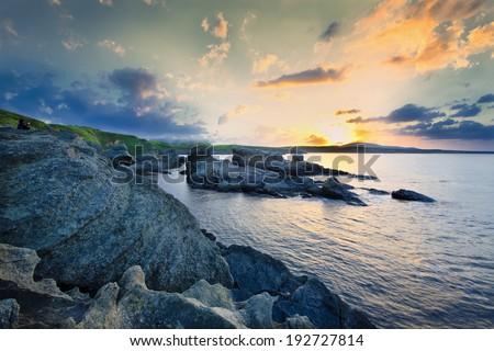 sunset on the rocky coast - stock photo