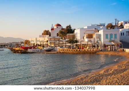 Sunset on the sea near the island of Mykonos in Greece and the night lights of restaurants and churches on the beach ... - stock photo