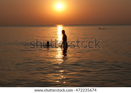Sunset on the sea. Silhouettes of mother with baby playing in the sea in the rays of the setting sun