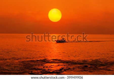 Sunset on the sea with a boat - stock photo