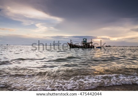 sunset on the sea with a boat  in drak cloud Silhouette  at Bangpra beach chonburi,thailand