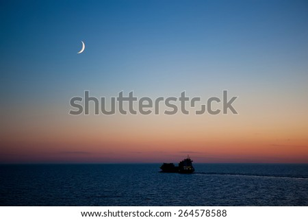 sunset on the sea with new moon - stock photo